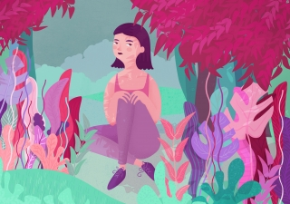Girl sitting in a forrest among plants