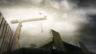 Crane on the dark construction site with two ravens flying around