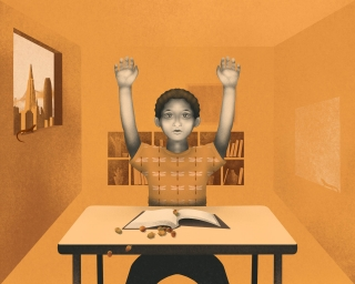 Boy at school classroom with hands up as he spill the acorns on his lesson book on the desk